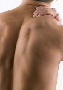 man rubbing his back to alleviate pain