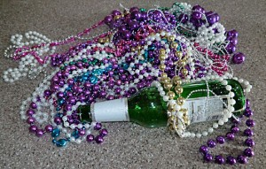 Mardi Gras beads and an empty beer bottle.